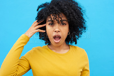 Buy stock photo Shot of a woman looking astonished while posing against a blue background