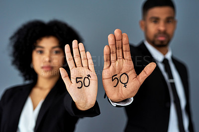 Buy stock photo Shot of businessman and businesswoman advocating for gender equality against a grey studio background