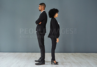 Buy stock photo Shot of young businessman and businesswoman standing back to back against a grey studio background