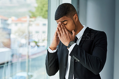 Buy stock photo Shot of a young businessman feeling stressed in a modern office