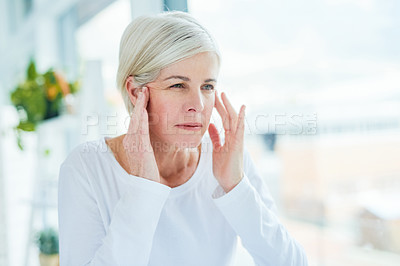 Buy stock photo Shot of a mature woman looking at her face in a bathroom mirror at home