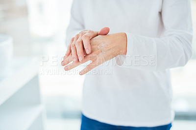 Buy stock photo Closeup shot of a mature woman applying hand cream in a bathroom at home