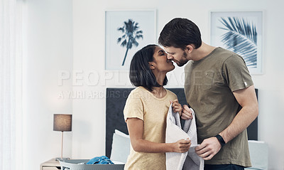 Buy stock photo Shot of an affectionate young couple doing laundry together at home