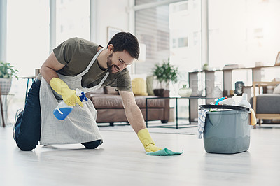 Buy stock photo Shot of a young man wiping the floor at home