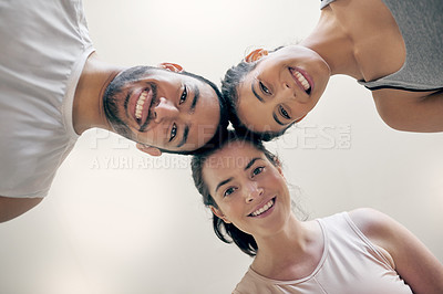 Buy stock photo Cropped shot of three young athletes standing together while looking down at the camera