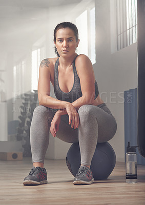 Buy stock photo Shot of a young female athlete sitting on a exercise ball in the gym