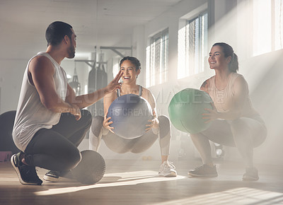 Buy stock photo Shot of two women using fitness balls while working out with their trainer