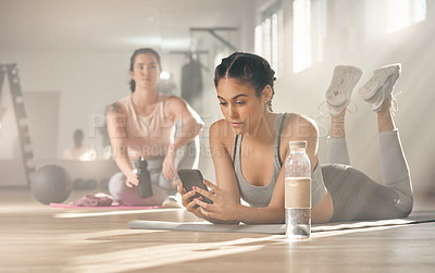 Buy stock photo Shot of a woman using her cellphone while on a break at the gym