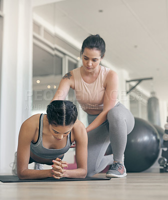 Buy stock photo Shot of a young woman working out with a personal trainer at the gym