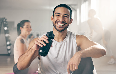 Buy stock photo Shot of a young male athlete drinking water while on a break at the gym