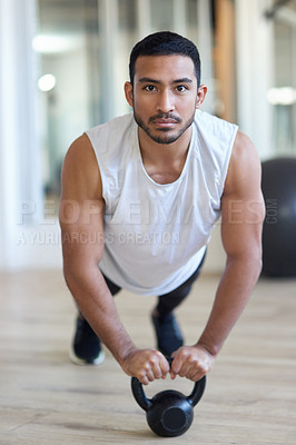 Buy stock photo Shot of a male athlete working out with a kettle bell