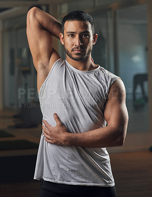 Buy stock photo Cropped portrait of a handsome young male athlete stretching in the gym