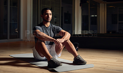 Buy stock photo Full length shot of a handsome young male athlete sitting on an exercise mat in the gym