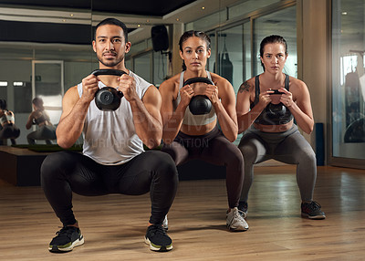 Buy stock photo Full length portrait of three young athletes working out with kettle bells in the gym