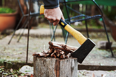 Buy stock photo Shot of an unrecognisable man chopping wood with an axe in preparation for a barbecue at home
