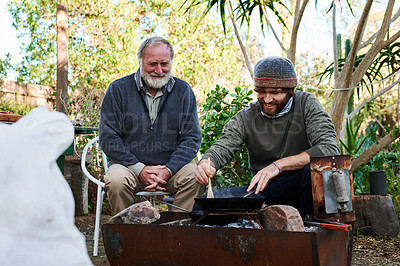 Buy stock photo Shot of a young man and his elderly father having a barbecue in their backyard at home