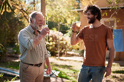 Buy stock photo Shot of a young man and his elderly father having drinks and a barbecue in their backyard at home