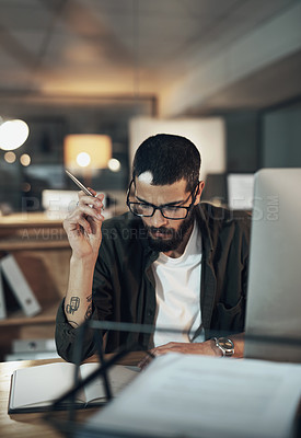Buy stock photo Shot of a young businessman writing in a notebook and using a computer during a late night in a modern office