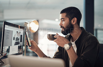 Buy stock photo Shot of a young businessman having coffee and using a smartphone during a late night in a modern office