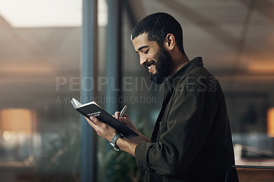 Buy stock photo Shot of a young businessman writing in a notebook during a late night in a modern office