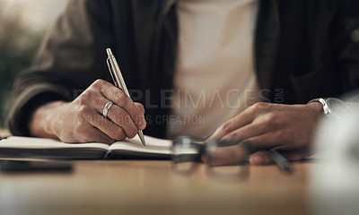 Buy stock photo Shot of an unrecognisable businessman writing in a notebook during a late night at work