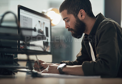 Buy stock photo Shot of a young businessman writing in a notebook and using a computer during a late night at work