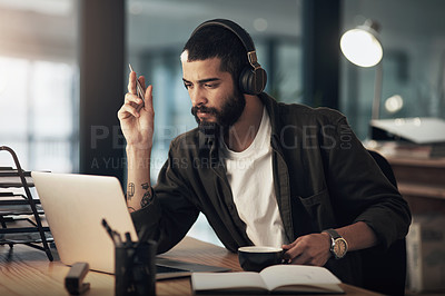 Buy stock photo Shot of a young businessman using a laptop and headphones during a late night at work