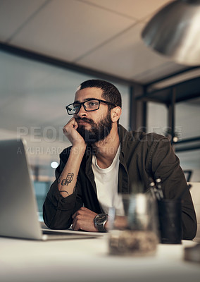 Buy stock photo Shot of a young businessman looking uncertain while working late at night in a modern office