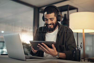 Buy stock photo Shot of a young businessman using a digital tablet, laptop and headphones during a late night at work