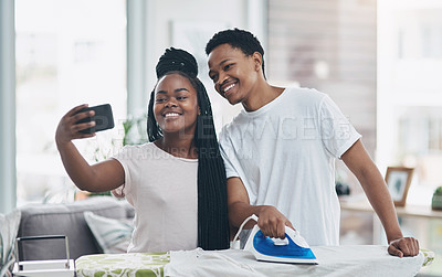 Buy stock photo Shot of a happy young couple taking selfies while ironing freshly washed laundry together at home
