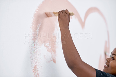 Buy stock photo Shot of a young woman painting a heart on a wall