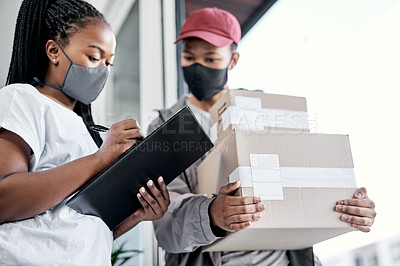 Buy stock photo Shot of a masked young woman signing for a delivery received at home