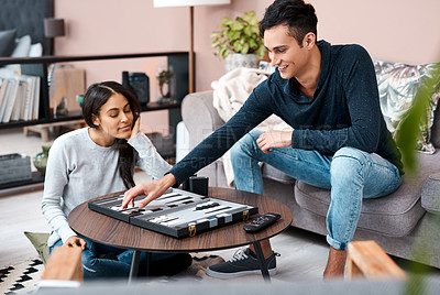 Buy stock photo Shot of a young couple playing a game of backgammon at home