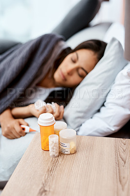 Buy stock photo Shot of a young woman recovering from an illness in bed at home