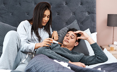 Buy stock photo Shot of a young woman taking her husband's temperature while recovering from an illness in bed at home