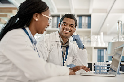 Buy stock photo Shot of two scientists working together on a laptop in a lab