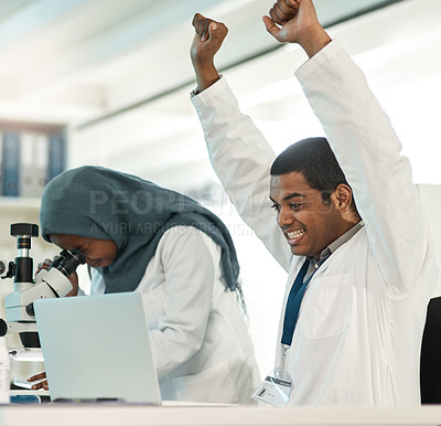 Buy stock photo Shot of a young scientist cheering while working on a laptop alongside a colleague in a lab