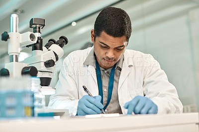 Buy stock photo Shot of a young scientist writing notes while working in a lab