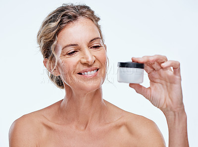 Buy stock photo Shot of a mature woman holding up a beauty product against a while background