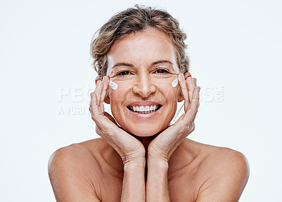 Buy stock photo Shot of a mature woman posing with moisturiser on her face