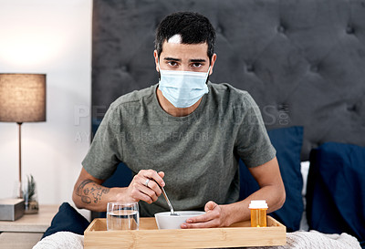Buy stock photo Shot of a masked young man having breakfast in bed while recovering from an illness at home