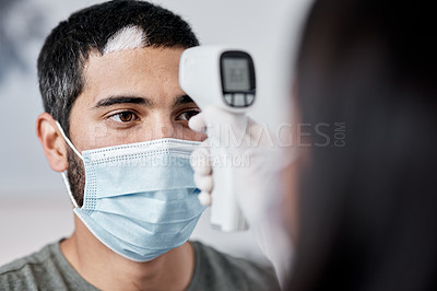 Buy stock photo Shot of a young man getting his temperature taken by his wife while recovering from an illness at home