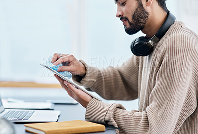 Buy stock photo Shot of a young man disinfecting his digital tablet while working from home