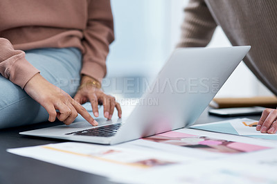 Buy stock photo Shot of an unrecognisable man and woman using a laptop while working from home