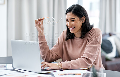 Buy stock photo Shot of a confident young woman using a laptop while working from home
