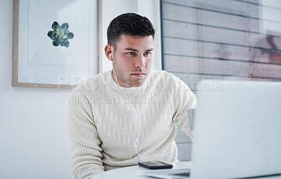 Buy stock photo Shot of a young man using a laptop while working from home