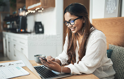 Buy stock photo Shot of an entrepreneur using her cellphone and laptop while working from a cafe