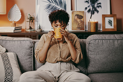 Buy stock photo Shot of a woman drinking coffee while relaxing on the sofa at home