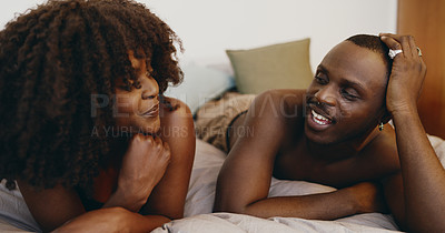 Buy stock photo Shot of a young couple relaxing and chatting in bed at home