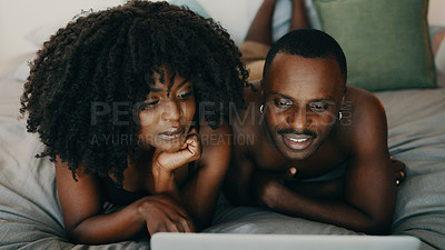 Buy stock photo Shot of a young couple using a laptop together in bed at home